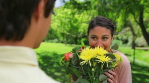stock-footage-smiling-woman-receiving-a-bunch-of-flowers-in-a-parkland
